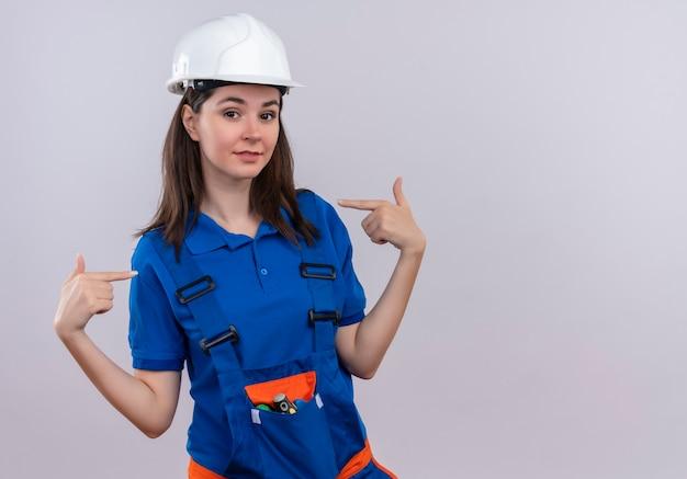 Zelfverzekerd jong bouwersmeisje met witte veiligheidshelm en blauw uniform wijst naar zichzelf met beide handen op geïsoleerde witte achtergrond met exemplaarruimte