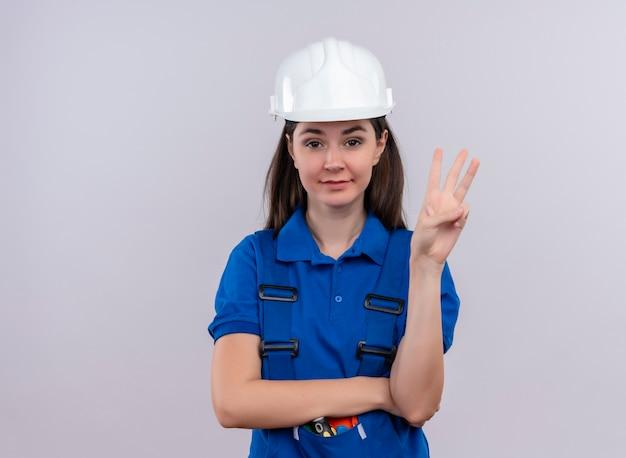 Zelfverzekerd jong bouwersmeisje met witte veiligheidshelm en blauwe uniforme gebaren drie met vingers op geïsoleerde witte achtergrond met exemplaarruimte