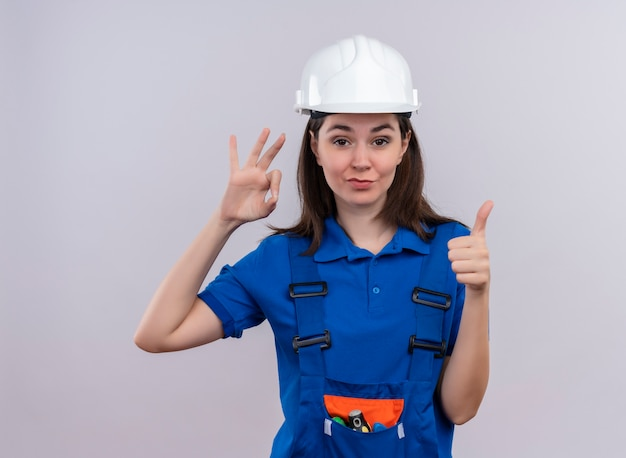 Zelfverzekerd jong bouwersmeisje met witte veiligheidshelm en blauwe uniforme gebaren ok en thums omhoog op geïsoleerde witte achtergrond met exemplaarruimte