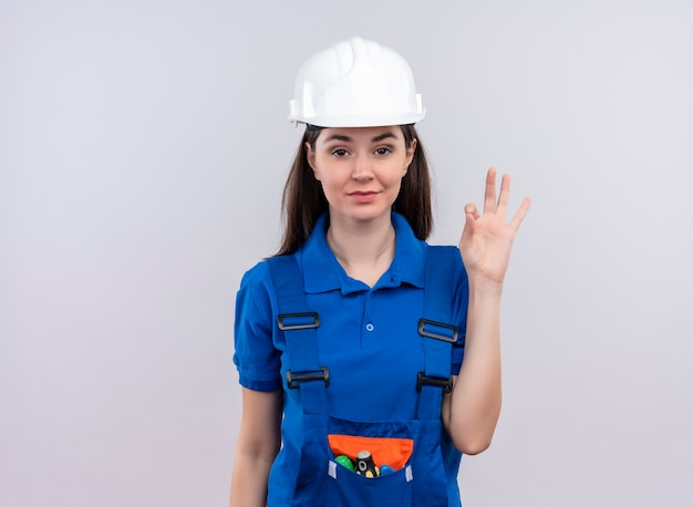 Zelfverzekerd jong bouwersmeisje met witte veiligheidshelm en blauwe uniforme gebaren ok op geïsoleerde witte achtergrond met exemplaarruimte