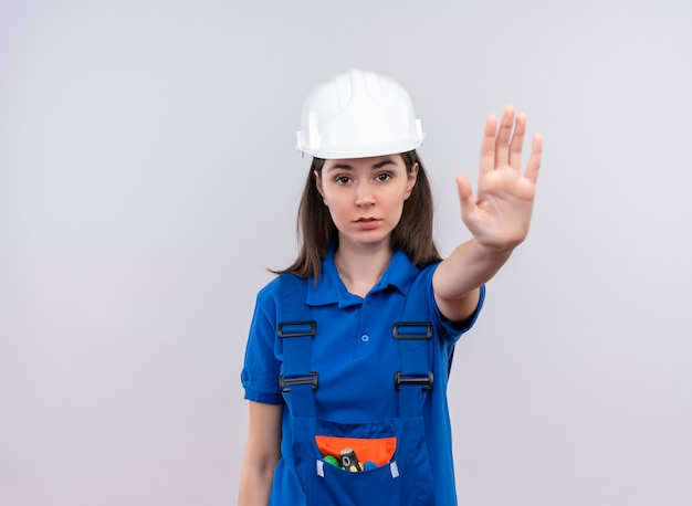 Zelfverzekerd jong bouwersmeisje met witte veiligheidshelm en blauwe uniforme gebaren stoppen op geïsoleerde witte achtergrond met exemplaarruimte