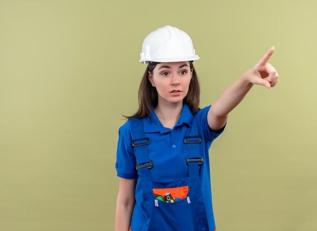 Zelfverzekerd jong bouwersmeisje met witte veiligheidshelm en blauwe uniforme punten vooruit op geïsoleerde groene achtergrond met exemplaarruimte