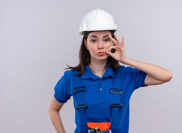 Zelfverzekerd jong bouwersmeisje met witte veiligheidshelm en blauwe uniforme ritssluitingen mond op geïsoleerde witte achtergrond