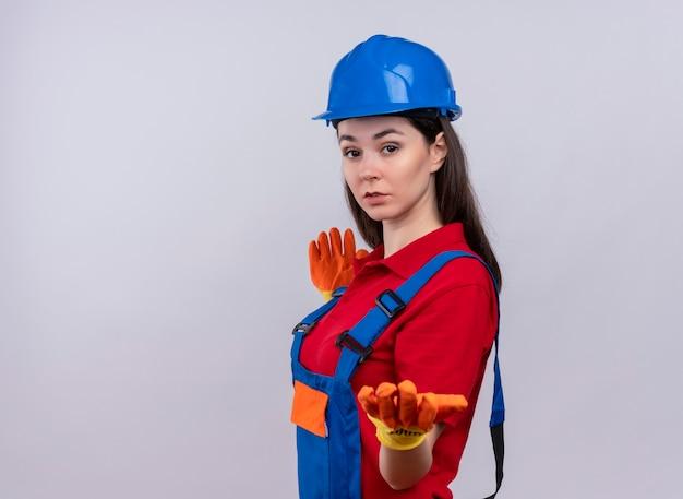 Zelfverzekerd jong bouwersmeisje staat zijwaarts en houdt op geïsoleerde witte achtergrond met exemplaarruimte uitdelen