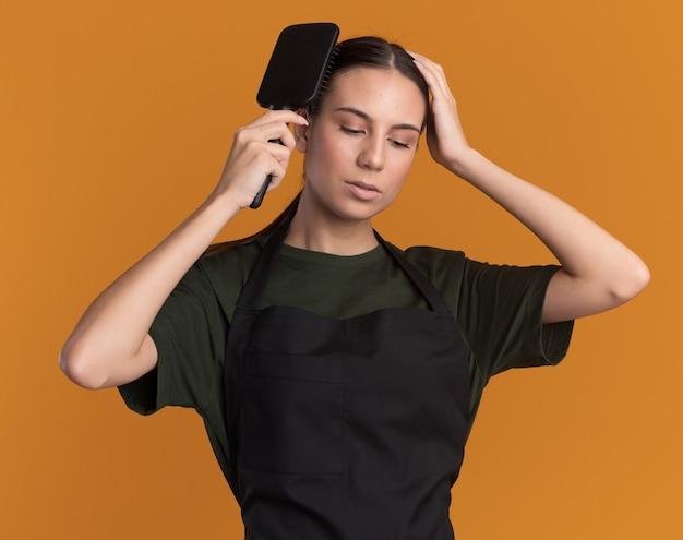 Zelfverzekerd jong brunette kappersmeisje in uniform dat haar kamt en hand op het hoofd legt geïsoleerd op een oranje muur met kopieerruimte