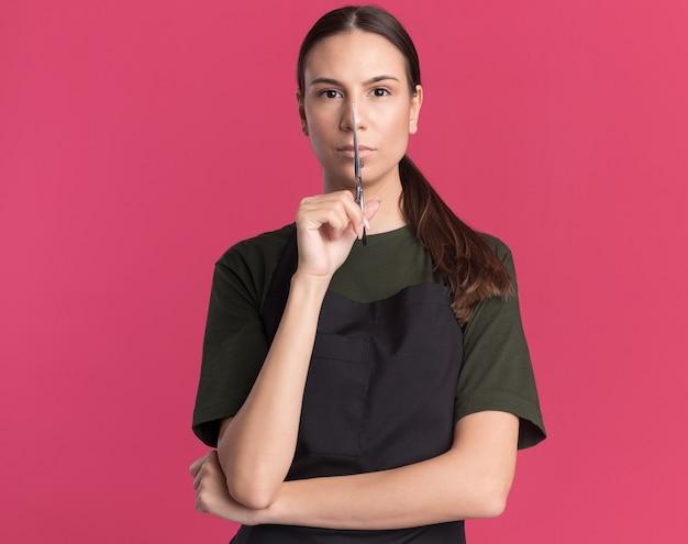 Zelfverzekerd jong brunette kappersmeisje in uniform houdt haaruitdunschaar voor gezicht