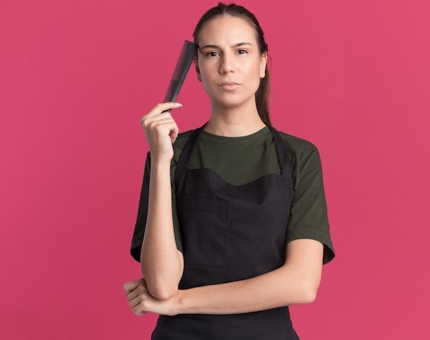 Zelfverzekerd jong brunette kappersmeisje in uniform houdt kam dicht bij gezicht