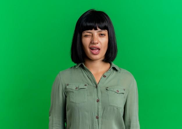 Zelfverzekerd jong brunette kaukasisch meisje knippert oog kijken camera geïsoleerd op groene achtergrond met kopie ruimte