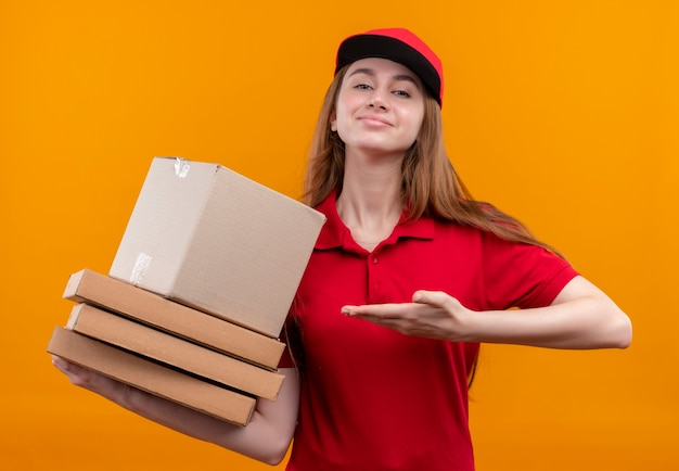 Zelfverzekerd jong de holdingsdoos en pakketten van het leveringsmeisje die met hand naar hen in rood uniform op geïsoleerde oranje ruimte richten