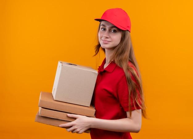 Zelfverzekerd jong de holdingsdoos en pakketten van het leveringsmeisje die zich in profielmening in rood uniform op geïsoleerde oranje ruimte bevinden
