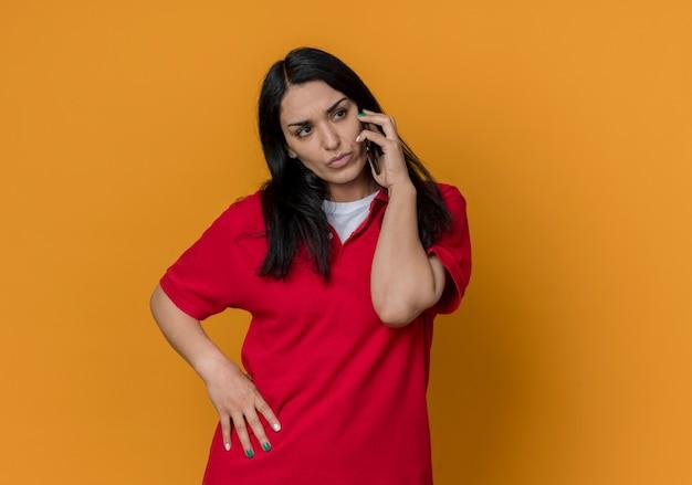 Zelfverzekerd jong donkerbruin kaukasisch meisje dat een rood overhemd draagt, spreekt aan de telefoon en kijkt naar kant die op oranje muur wordt geïsoleerd