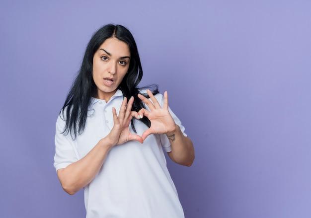 Zelfverzekerd jong donkerbruin kaukasisch meisjesgebaren harthandteken dat op purpere muur wordt geïsoleerd