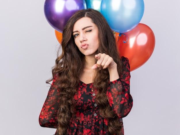 Zelfverzekerd jong feestmeisje met ballonnen achter de rug kijkend en wijzend knipogend geïsoleerd op een witte muur