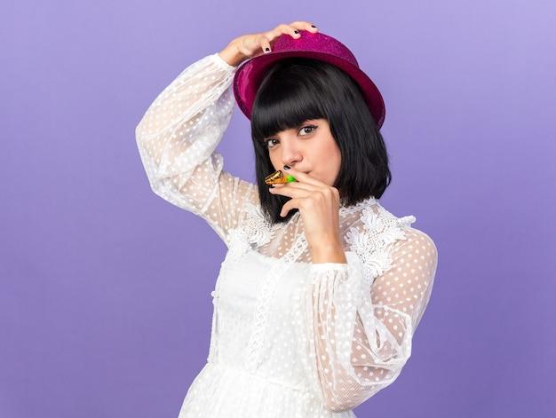 Zelfverzekerd jong feestmeisje met feestmuts met feesthoorn in mond die hoed opsteekt geïsoleerd op paarse muur