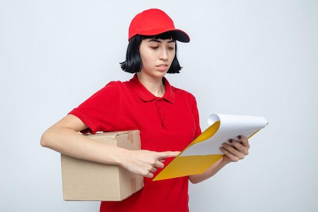 Zelfverzekerd jong kaukasisch bezorgmeisje dat kartonnen doos vasthoudt en naar klembord kijkt