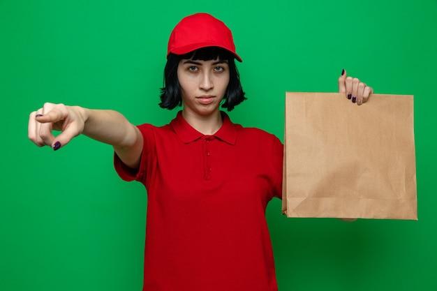 Zelfverzekerd jong kaukasisch bezorgmeisje dat voedselverpakkingen vasthoudt en naar de zijkant wijst