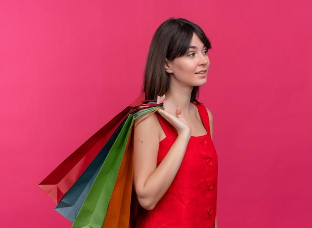 Zelfverzekerd jong kaukasisch meisje houdt pakketten gooien ze op schouder op geïsoleerde roze achtergrond