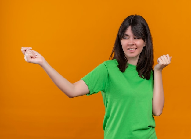 Zelfverzekerd jong kaukasisch meisje in groen shirt beweert iemand op geïsoleerde oranje achtergrond met kopie ruimte te bellen