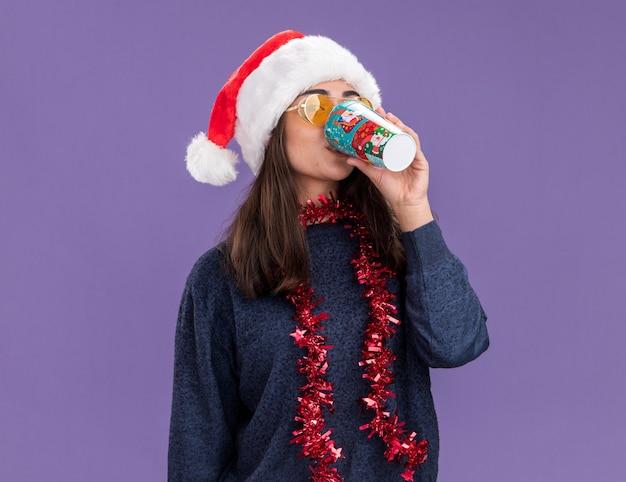 Zelfverzekerd jong kaukasisch meisje in zonnebril met kerstmuts en slinger om nek drankjes uit papieren beker geïsoleerd op paarse achtergrond met kopie ruimte