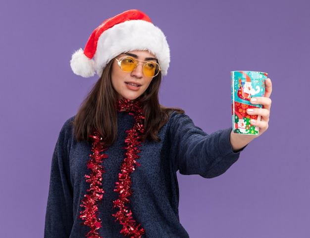 Zelfverzekerd jong kaukasisch meisje in zonnebril met kerstmuts en slinger om nek houdt en kijkt naar papieren beker geïsoleerd op paarse muur met kopieerruimte