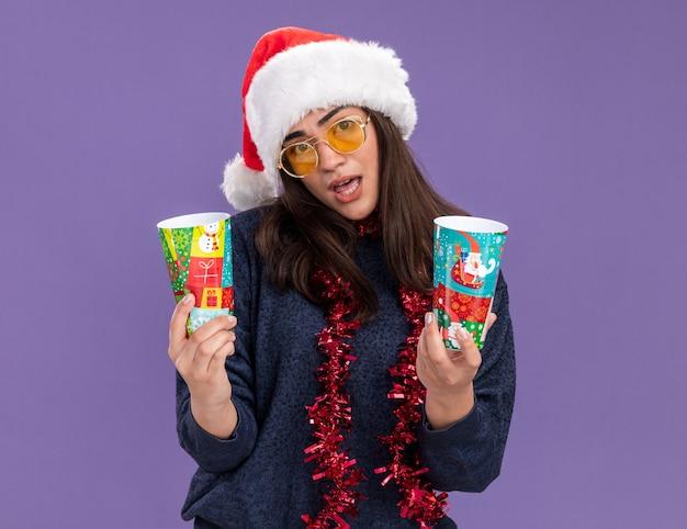 Zelfverzekerd jong kaukasisch meisje in zonnebril met kerstmuts en slinger om nek houdt papieren bekers geïsoleerd op paarse muur met kopieerruimte
