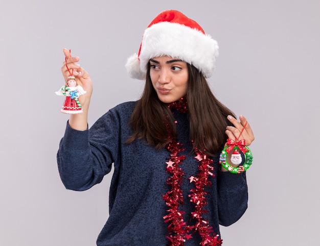 Zelfverzekerd jong kaukasisch meisje met kerstmuts en slinger om de nek houdt en kijkt naar kerstboomspeelgoed geïsoleerd op een witte muur met kopieerruimte
