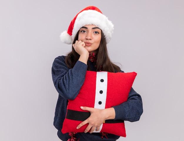 Zelfverzekerd jong kaukasisch meisje met kerstmuts en slinger om nek houdt versierd kussen en zet vuist op kin