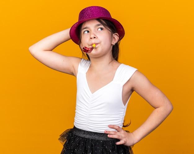 Zelfverzekerd jong kaukasisch meisje met paarse feestmuts die hand op het hoofd zet en feestfluitje blaast, kijkend naar kant geïsoleerd op oranje muur met kopieerruimte