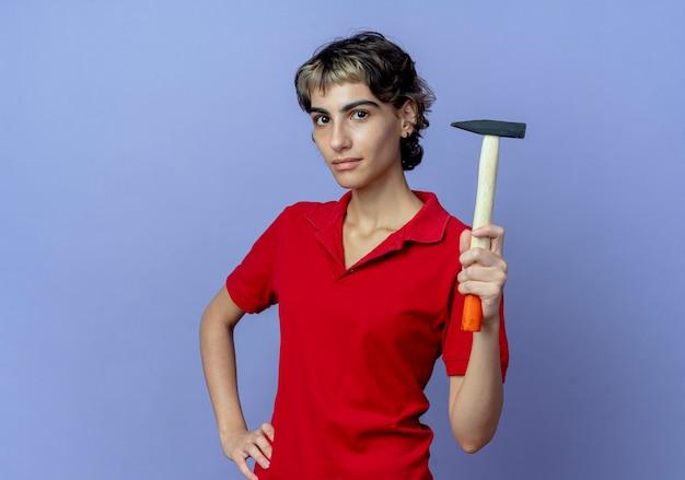 Zelfverzekerd jong kaukasisch meisje met pixie kapsel bedrijf hamer en hand zetten taille geïsoleerd op paarse achtergrond met kopie ruimte