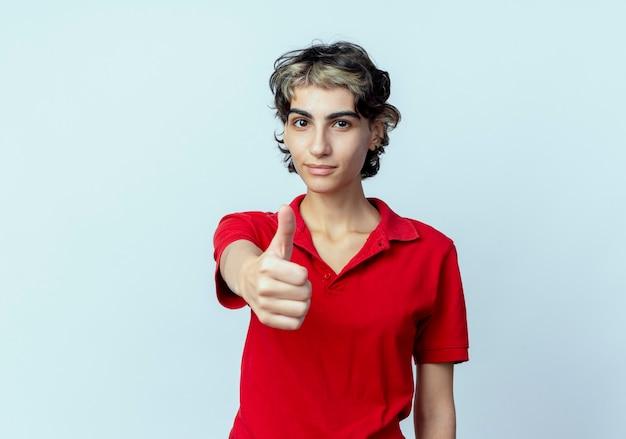Zelfverzekerd jong kaukasisch meisje met pixiekapsel dat uit hand uitrekt bij camera die duim toont die omhoog op witte achtergrond met exemplaarruimte wordt geïsoleerd