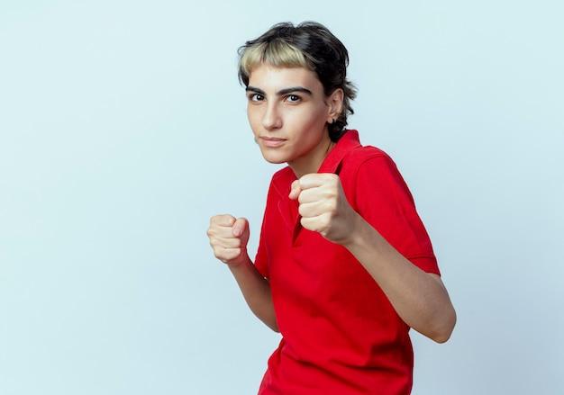 Zelfverzekerd jong kaukasisch meisje met pixiekapsel die boksgebaar doen dat op witte achtergrond met exemplaarruimte wordt geïsoleerd