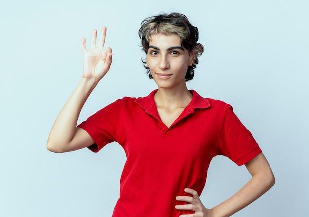 Zelfverzekerd jong kaukasisch meisje met pixiekapsel die hand op taille zetten en ok teken doen dat op witte achtergrond wordt geïsoleerd