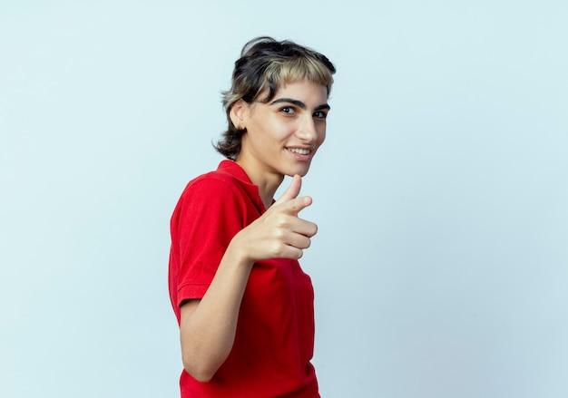 Zelfverzekerd jong kaukasisch meisje met pixiekapsel die zich in profielmening bevinden die op camera richten die op witte achtergrond met exemplaarruimte wordt geïsoleerd