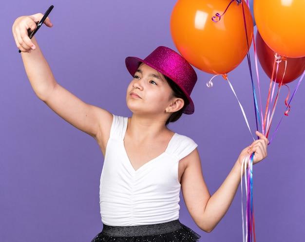 Zelfverzekerd jong kaukasisch meisje met violet feestmuts dat heliumballonnen vasthoudt en selfie neemt op telefoon geïsoleerd op paarse muur met kopieerruimte