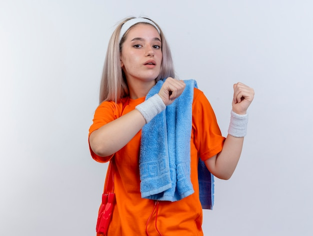 Zelfverzekerd jong kaukasisch sportief meisje met beugels en met touwtjespringen om de nek met hoofdband en polsbandjes met handdoek op schouder wijst terug met twee handen op witte muur