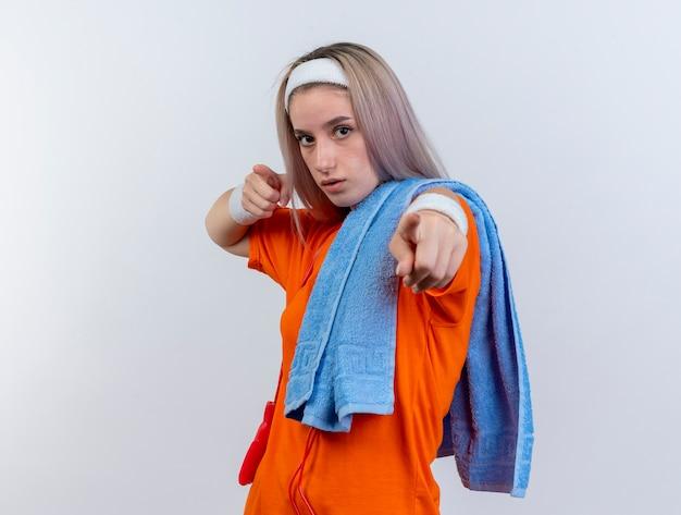 Zelfverzekerd jong kaukasisch sportief meisje met beugels en met touwtjespringen om nek dragen hoofdband polsbandjes handdoek op schouder punten met twee handen op witte muur houden