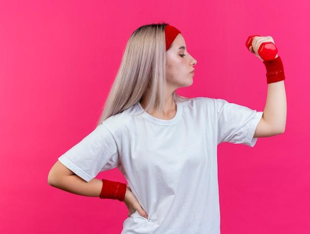 Zelfverzekerd jong kaukasisch sportief meisje met beugels met hoofdband en polsbandjes houdt halter vast en kijkt naar de zijkant