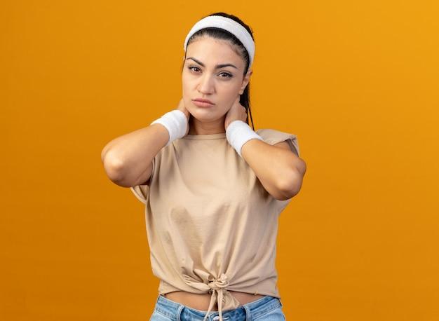 Zelfverzekerd jong kaukasisch sportief meisje met hoofdband en polsbandjes die de handen achter de nek houden en naar de voorkant kijken geïsoleerd op een oranje muur met kopieerruimte