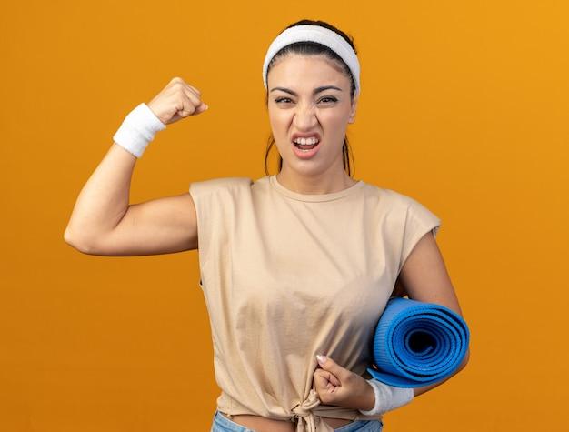 Zelfverzekerd jong kaukasisch sportief meisje met hoofdband en polsbandjes met fitnessmat die naar de voorkant kijkt en een sterk gebaar doet dat op een oranje muur wordt geïsoleerd
