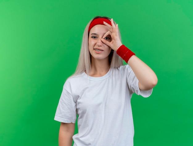 Zelfverzekerd jong kaukasisch sportief meisje met steunen die hoofdband dragen