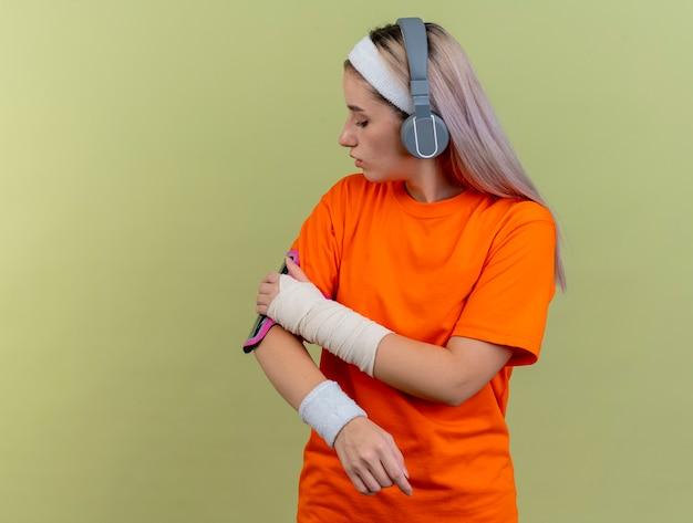 Zelfverzekerd jong kaukasisch sportief meisje op koptelefoon met hoofdband en polsbandjes kijkt en legt de hand op de armband van de telefoon