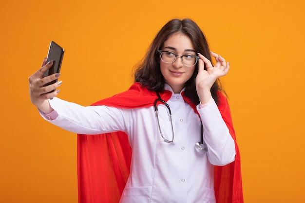 Zelfverzekerd jong kaukasisch superheldmeisje in rode cape met doktersuniform en stethoscoop met een bril die een bril grijpt en selfie neemt
