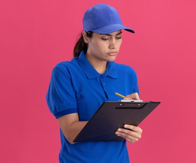 Zelfverzekerd jong leveringsmeisje die eenvormig met glb dragen die iets op klembord schrijven dat op roze muur wordt geïsoleerd