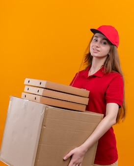 Zelfverzekerd jong leveringsmeisje in rode eenvormige holdingsdoos en pakketten op geïsoleerde oranje ruimte
