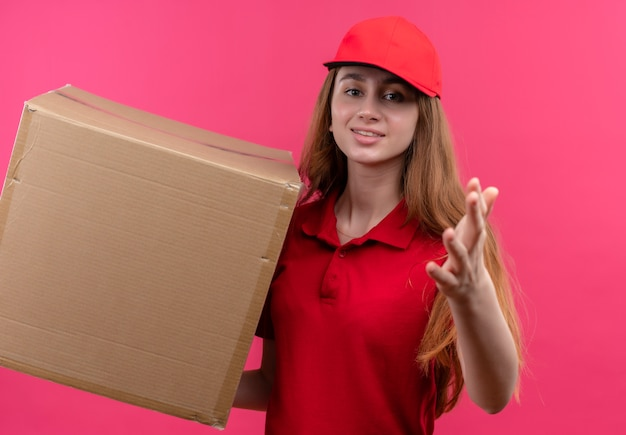Zelfverzekerd jong leveringsmeisje in rode uniforme holdingsdoos en het uitrekken zich uit op geïsoleerde roze ruimte