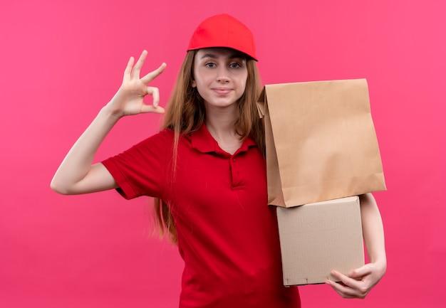 Zelfverzekerd jong leveringsmeisje in rode uniforme holdingsdozen en doet ok teken op geïsoleerde roze ruimte