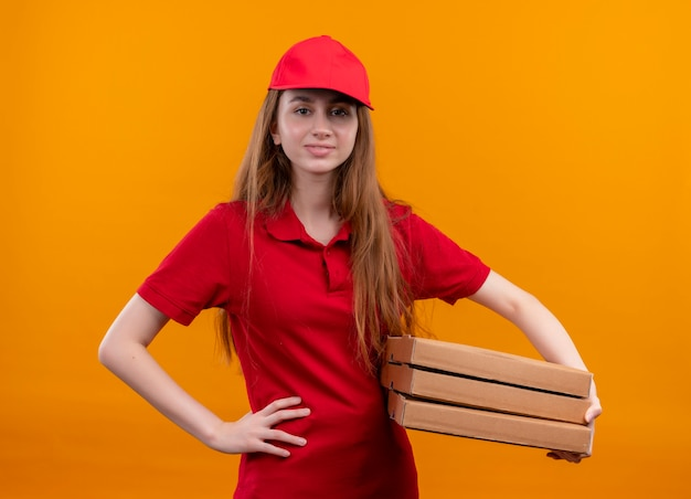 Zelfverzekerd jong leveringsmeisje in rode uniforme holdingspakketten met hand op taille op geïsoleerde oranje ruimte