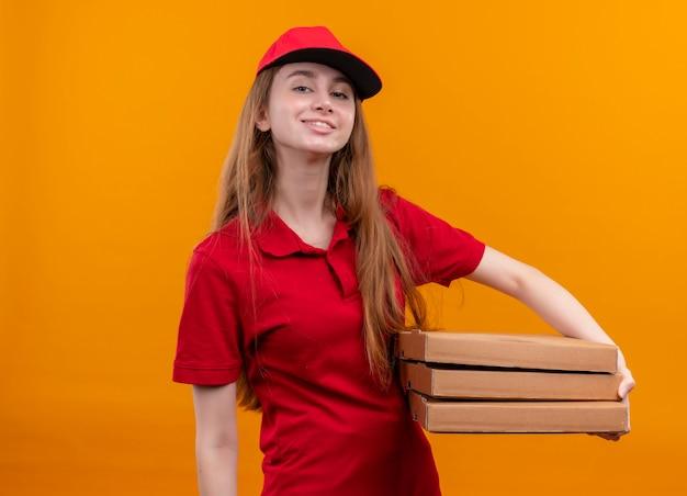 Zelfverzekerd jong leveringsmeisje in rode uniforme holdingspakketten op geïsoleerde oranje ruimte