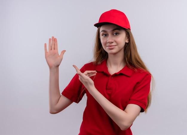Zelfverzekerd jong leveringsmeisje in rood uniform dat hand opheft en op het op geïsoleerde witte ruimte richt
