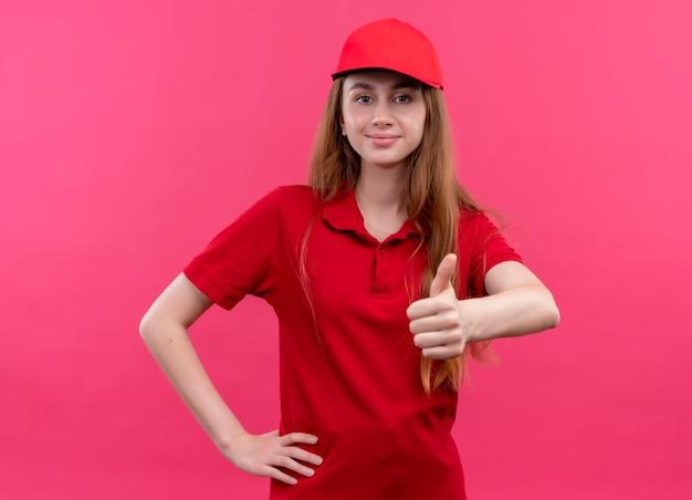 Zelfverzekerd jong leveringsmeisje in rood uniform die duim opdagen en hand op taille op geïsoleerde roze ruimte zetten